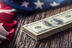 I dollari americani gli S.U.A. diminuiscono Chiuda su della bandiera americana e del denaro contante del dollaro sul vecchio legn Immagini Stock