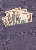I dollari di fatture in jeans neri appoggiano la tasca Fotografia Stock