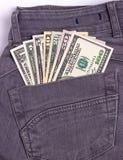 I dollari di fatture in jeans neri appoggiano la tasca Immagine Stock