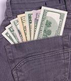I dollari di fatture in jeans neri appoggiano la tasca Fotografia Stock Libera da Diritti