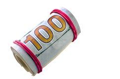 I dollari hanno rotolato in un tubo su un fondo bianco Immagine Stock