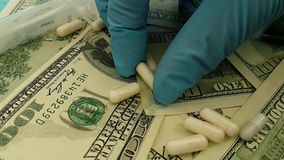 I dollari incapsula il farmaco antibiotico di concetto dei guanti della mano, fucilazione lenta stock footage
