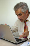 I don't believe it!. A businessman looks at the screen of his laptop and holds out his hands in amazement. What's the pesky machine up to now Royalty Free Stock Photography
