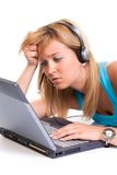 I don't get it... Beautiful confused teenage girl, with a laptop and headphones, on white background Royalty Free Stock Images