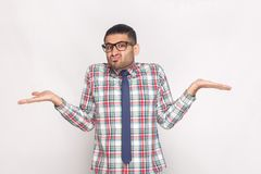 I don`t know. confused bearded businessman in checkered shirt, b. Lue tie and eyeglasses standing, raised arms and looking at camera with doubtful face. studio royalty free stock image