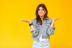 I don`t know. Portrait of confused beautiful brunette young woman with makeup in denim casual style standing with raised arms, royalty free stock photography