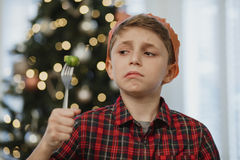 But I Don`t Like Brussel Sprouts!. Little boy is holding a brussel sprout on his fork at christmas time. He is wearing a party hat and is grimacing at the royalty free stock images