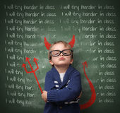 I don't think I will try harder in class. Naughty devil schoolboy with lines written on a blackboard reading I will try harder in class and devils horns, tail royalty free stock images
