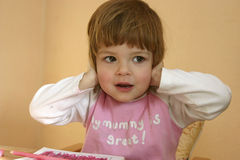 I don't wanna hear this, mummy!. Little, cheeky girl covering her ears with her hands Stock Images