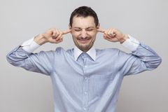 Free I Don`t Want To Hear It. Angry Bristle Businessman In Classic Blue Shirt Standing, Closed Eyes And Puting Fingers On Ears To Royalty Free Stock Photos - 135716828