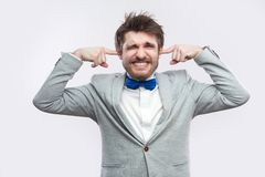 I don`t want to hear. Portrait of worried handsome bearded man in casual grey suit, blue bow tie standing with closed eyes and. Putting fingers in ears. studio stock photo