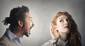 I don't want to hear you. A men is screaming into a woman's ear while she's trying to listen to him Stock Photo