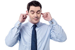 I don't want to listen. Businessman plugging ears with fingers stock images