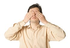 I don't want to see. A man covering his eyes with his hands Stock Image