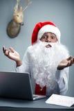 I dont know. Man wearing Santas hat and beard separating hands and looking at camera Royalty Free Stock Photos