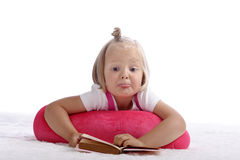 I dont' understand anything. Little girl lying on the floor making faces Stock Photo