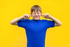 I dont want hear you! Sadness ginger boy holding fingers on ea. Rs and closed eyes. Isolated on yellow background stock image