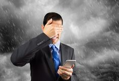 I dont want to answer this business call. Portrait of a businessman covering his eyes because he dont want to look the phone caller with cloudy and stormy day in Stock Photos