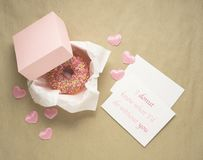 I donut know. Creative valentine day concept photo of donut in box with hearts and notes with text on craft brown background Stock Photo
