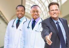 I dottori Behind Businessman Reaching della corsa mista per la scossa della mano dentro Fotografia Stock Libera da Diritti