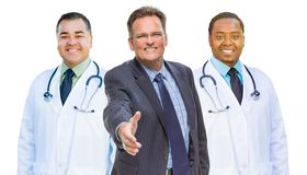 I dottori Behind Businessman Reaching della corsa mista per la scossa della mano sopra Fotografia Stock