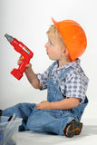 I am drilling a whole. Cute toddler boy with a toy power drill and a hard hat pretending to drill a whole stock image