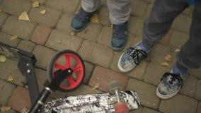 I due adolescenti sono intorno ad un bordo e ad un mestolo del penny Nella struttura, soltanto nelle gambe e nel motorino su cui  archivi video