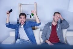 I due amici attraenti sono divertenti con la gioco-stazione Immagini Stock