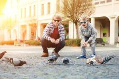 I due fratelli alimentano le colombe sul vecchio quadrato di città Immagini Stock Libere da Diritti