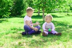 I due fratelli giocano con le bolle di sapone e di un cane nel parco Fotografie Stock
