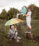 I due fratelli giocano in pioggia all'aperto retro pubblicano fotografia stock libera da diritti