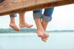 I due fratelli hanno oscillato le loro gambe dal pilastro di legno Vacanza di famiglia sul lago immagine stock