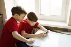 I due fratelli stanno sedendo nella cucina e stanno giocando con il telefono immagine stock