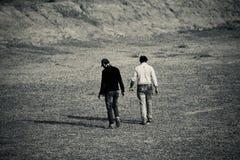 I due giovani stanno camminando due nella direzione - fotografia di riserva Fotografie Stock
