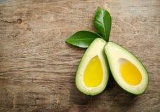 I due halfs freschi dell'avocado gradiscono una ciotola per olio Immagini Stock