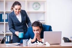 I due impiegati che soffrono nel luogo di lavoro immagine stock libera da diritti