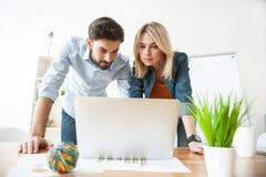 I due lavoratori abili stanno utilizzando un computer portatile Fotografia Stock