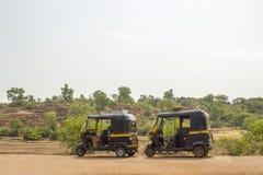 I due neri ed i risciò indiani gialli del motore stanno su una strada asfaltata contro lo sfondo di una collina e di una foresta  immagine stock