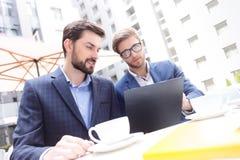 I due uomini d'affari attraenti stanno lavorando in collaborazione Fotografia Stock