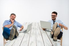I due uomini d'affari con le gambe sopra la tavola che lavora ai computer portatili Fotografia Stock
