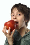 I am eating an apple. The girl which is eating the big red apple Royalty Free Stock Images