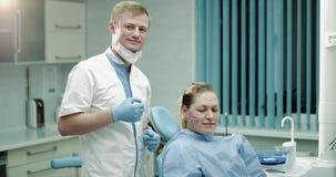 I en modern klinikrumdoktor och hennes tålmodiga mogna kvinna var jätteglad efter ett tillvägagångssätt av mikro-needling, eller stock video