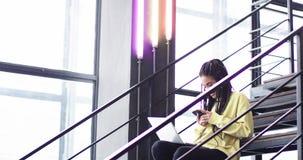 I en modern kontorsmitt härlig afrikansk dam som arbetar på hennes bärbar dator och förresten använder hennes smartphone och att  lager videofilmer
