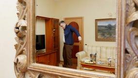 I en reflexion av en stor härlig spegel sätter en ung stilig man, en affärsman på ett omslag, förbereder sig för lager videofilmer