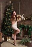 i `en s för det nya året står dekorerad vardagsrum med en julgran av en klassisk inre flickan le med gåva arkivbilder