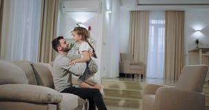 I en stor rymlig vardagsrum en ung farsa som spelar med hans lilla dotter i soffan, liten flicka som över hoppar till stock video
