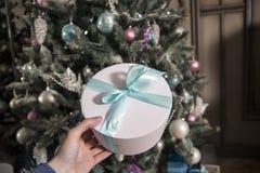 I en vit ask för hand med en gåva Flickan med en gåva Nytt års gran-träd mot bakgrunden av arkivbild