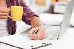 I am enjoying hot drink during hard work. Close up of hands of office worker holding cup and drinking tea. The man is sitting at desk near laptop. He is writing Royalty Free Stock Image