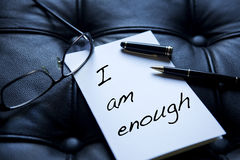 I Am Enough written on paper. Next to pen and eyeglasses on black leather royalty free stock photos
