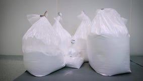 I ett rent lagerrum medicinsk produktion Den vita vikten är emballerad på stora plastpåsar Denna ingrediens lager videofilmer